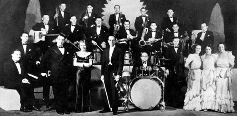 Ambrose and His Orchestra in 1935. Ambrose is at the center, with Elsie Carlisle and Sam Browne to the left and the Rhythm Sisters to the right.